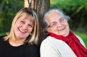 Tochter pflegt Mutter gemeinsam lachend in der Natur midlife coaching
