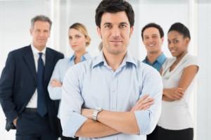 Zufriedener Mitarbeiter steht mit verschränkten Armen  vor seinen Kolleginnen und Kollegen