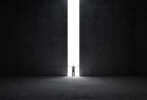 Mann schiebt riesige Tür auf und guckt aus dem Dunkel ins Licht