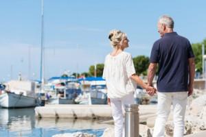 Glückliches älteres Paar läuft im Sommer am Hafen an Fischerbooten entlang