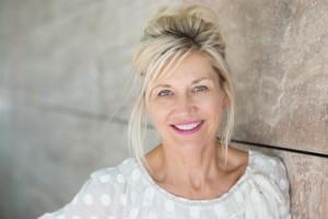attraktive ältere Frau lehnt an Wand und lacht, nach Midlife Krise wieder glücklich