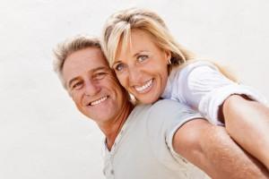 Mann hat Frau huckepack am Strand glücklich nach Midlife Coaching