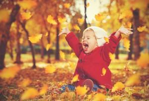 Kind sitzt im Herbstlaub und freut sich des Lebens
