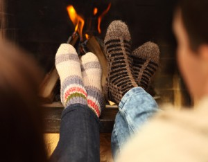 Nahaufnahme von Beinen eines Paars mit dicken Socken vor einem Kamin