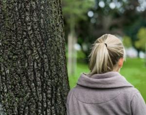 nachdenkliche junge Frau von hinten an Baum gelehnt