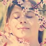 Kind riecht an Kirschblüte und genießt