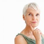 attraktive mitfünfzigerin mit kurzen weißen haaren und zeigefinder am Kinn