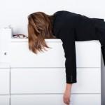 Frau liegt erschöpft auf Schreibtisch interessierte Selbstgefährdung