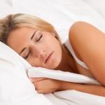 Eine junge hübsche Frau schläft im Bett und erholt sich.