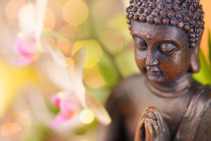 Metta Meditation - Selbstmitgefühl durch Meditation. Buddha Figur aus Ton mit vor der Brust gefalteten Händen neben unscharfen Lotusblumen