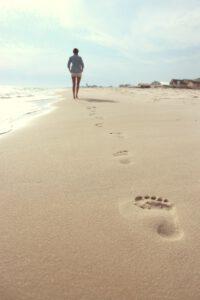 Schritte Fußabdrücke im Sand von Frau, die Richtung Sonne geht
